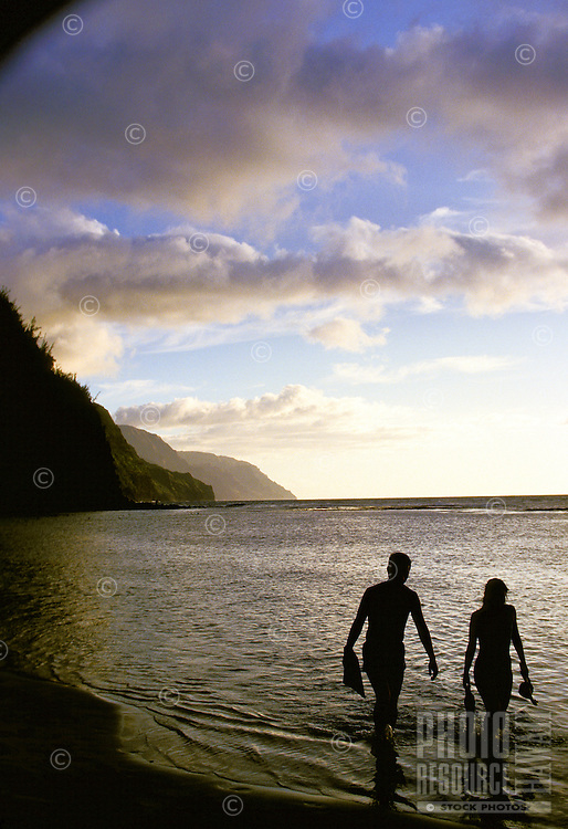 At dusk, a couple walks on the beach at Haena, Kauai, carrying fins and snorkels