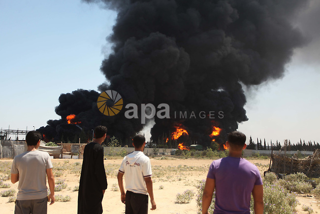 Palestinian men stand looking as flames engulf the fuel tanks of the only power plant supplying electricity to the Gaza Strip after it was hit by overnight Israeli shelling, on July 29, 2014, in the south of Gaza City. The damage of the power plant exacerbated the heavy damage to civilian infrastructure in Gaza already inflicted during the 22 days of the Israeli offensive aimed at stamping out militant rocket fire and destroying attack tunnels. . Photo by Ashraf Amra