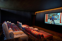 A luxury home cinema furnished with chairs upholstered in a striped fabric with matching cushions