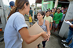 Kaitlin Lee-Bun (left) hands a water filter to a woman in Tanauan, a city in the Philippines province of Leyte that was hit hard by Typhoon Haiyan in November 2013. The storm was known locally as Yolanda. The distribution of water filters was sponsored by the United Methodist Committee on Relief, a member of the ACT Alliance. UMCOR and other ACT members are working throughout the affected region to help people recover and rebuild in the wake of the massive storm.