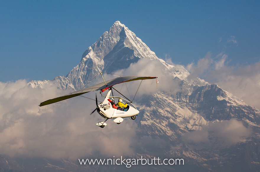 Microlight flight towards the foothills of the Himalayas, with Machapuchare or Fish-tail Mountain in the background. Pokhara, Nepal.