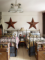 An industrial table and a 1960s French stool sits between the twin beds in Aidan's room which is decorated with stars found in a flea market