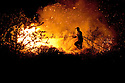 A fireman takes great risks running into a wild fire trying to stop it from crossing a road into yet another valley during a season of many wild fires in the Peloponnese, Greece;