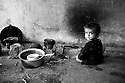 A young child sits by the makeshift cooking fire in the Pepri storage building now housing hundreds of families affected by the floods. Karachi, Pakistan, 2010