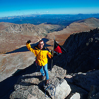 Smiling male hiker with a flag waves from the summit of Mt. Evans. Colorado.