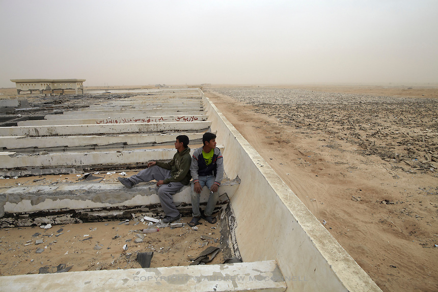 Stone collectors take a cigarette break on the roof of the main terminal building of Yasser Arafat International Airport in southern Gaza. The airport was destroyed by Israeli warplanes in 2001 and 2002, and has become a source of building materials for much needed  reconstruction in Gaza.