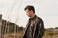 man wearing a leather jacket walking in tall grass