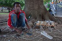 Italy. Lombardy Region. Como. Homeless african migrants living in the park below the San Giovanni railway station. An ethiopian minor boy (17 years old) is charging his mobile phone. 10.08.2016 © 2016 Didier Ruef