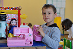 A Roma boy playing with a toy sewing machine in the Nasa Radost preschool in Smederevo, Serbia. The preschool focuses on Roma and children from other vulnerable situations.