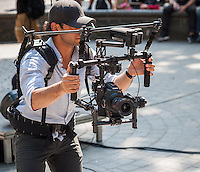 A videographer uses a Canon Eos C camera, on a stability rig with gimbal, in New York on Tuesday, June 21, 2016. (© Richard B. Levine)