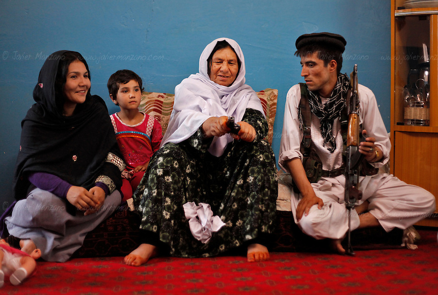 Commander Kaftar (at center) clears the chamber of her revolver at a the safe house she now lives in on the outskirts of Pul-e Khumri, a small city in Bahglan province in Afghanistan. Nadera (at far left) lets the former commander stay at her home. <br />