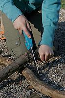 Kinder basteln Klangspiel aus Ästen, Äste werden auf richtige Länge gesägt