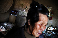 Wang Bao Ying stands in her home in Fanzhuang Village, Gangyun County, Jiangsu, China, crying as she describes her grandson's life.  Wang Bao Ying is the grandmother of the orphan boy Fan Lu Yang, 10, whom she cares for with husband Fan Qing Huai.  The grandparents are both over 75 and often ill, and the income from growing corn, wheat, and hay, cannot support the three.  Fan Lu Yang's father died in 2000 in an accident at a small coal mine and his mother developed dementia and disappeared about a year before this picture was taken...At the time of the picture, China's Amity Foundation charity, was investigating the family's situation in preparation to raise money to financially support these children and other orphans in similar situations.  With Amity's support, each orphan, aged 6-12, would receive approximately 1,400 RMB annually (about 200 USD) to pay for the cost of living. Amity works to keep children out of the institutional orphanages in China, preferring to provide monetary assistance that can help maintain a family environment for the orphans it helps.