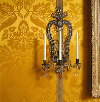 A Louis XIV-style crystal sconce has been placed on gold metal braid against the golden yellow damask that covers the walls of the drawing room