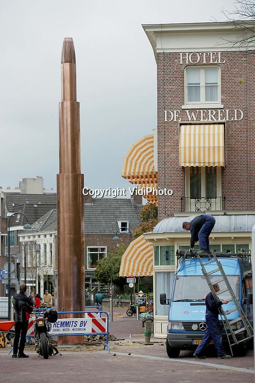 """Foto: VidiPhoto..WAGENINGEN - Tussen Hotel De Wereld en het Vrijheidsmonument, heeft de gemeente Wageningen vrijdagmiddag het omstreden """"Vrijheidsvuur"""" geplaatst. Het gaat om een proefopstelling, zodat inwoners zich een beeld kunnen vormen over hoe de koperen paal er uit komt te zien. In de volksmond wordt het 100.000 euro kostende kunstwerk """"De penis van Bernhard"""" genoemd, omdat het een eerbetoon moet zijn aan de overleden Prins Bernhard. Een groot deel van de bevolking is tegen dit -volgens hen- te moderne en te dure ontwerp."""
