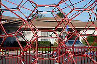 A climbing rope net play structure at Circle Park, a pocket park located on Park Circle Drive in Anaheim, California.  This image is a closeup showing the symmetry and tying mechanisms used for the red rope.