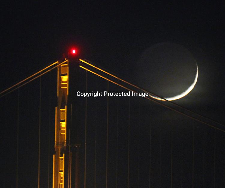 The crescent moon setting behind Golden Gate Bridge as seen from Aquatic Pier, San Francisco, CA.
