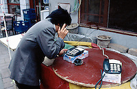 China. Province of Beijing. Beijing. A woman uses a public pay phone box in the street.  © 2004 Didier Ruef
