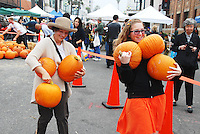 People carry pumpkins down a 25-foot runway during the 'All You Can Carry Pumpkin Patch for $5.00' at the Santa Monica Farmers Market on Wednesday, October 31, 2012.
