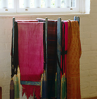 Coloured wool shawls are to hand for guests who feel the cold on a stand painted in faux lapis lazuli beneath a window in the living room