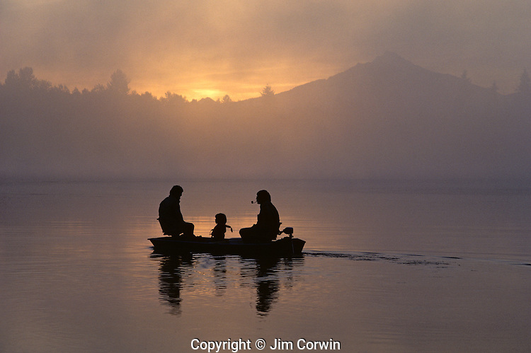 Sunrise at Lake Cassidy with Mount Pilchuck in fog with silhouetted fishermen and small boy in small rowboat getting ready to fish, east of Marysville, Washington State USA.