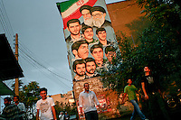 A billboard featuring the present supreme leader of Iran Ali Khamenei (L) and the spiritual leader of the Iranian revolution, Ayatollah Khomeini (R). Below them are portraits commemorating some of the young Martyrs of the Iran-Iraq war.