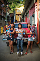 15-year old, Yanaifre Acevedo, (center) poses for a portrait in a slum in Caracas, Venezuela holding her newborn son, Dilan, with her sister, Keisy (right), who also got pregnant with her son John, when she was 15 years old, and their friend Diovile Toro, 19 years old, with her 5-month old daughter, Diovelys.