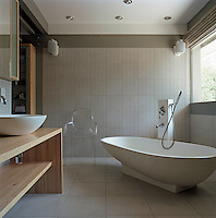 "An Agape 'Spoon"" bath tub dominates this spartan bathroom which is furnished with a Philippe Starck Ghost chair"