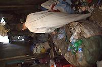 2011 Mokattam Garbage City (alla periferia del Cairo) il quartiere copto dove si vive in mezzo alla spazzatura raccolta: interno, un uomo di spalle tra i sacchi dell'immondizia.