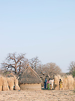 A family of the Nuba tribe outside their mud hut house in the village of Nyaro, Kordofan region, Sudan.