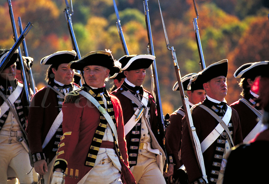 Redcoats with muskets and tricorn hats pass in review; march left to right; officer looks right; reenactment of battle of Yorktown. New York USA Pound Ridge Reservation.