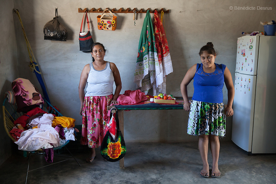 "Xhunaxhi Rosalía Santiago López (R) portrayed with her mother Antonia López Guerra (L) at their home in Santa María Xadani, Oaxaca, Mexico on February 18, 2016. Xhunaxhi – her name means ""virgin"" in Zapotec – is 14 and lives with her 18-year-old partner and her mother, who had her own first child aged 17, in the town of Santa María Xadani in the southern Mexican state of Oaxaca. Xhunaxhi, who speaks little Spanish, is painfully shy and childlike and punctuates her comments with giggles. She is five months pregnant, but seems not to really understand – she has to ask her mother when her baby is due. She left school at 10 to travel with her family to Tepic, in the western state of Nayarit, for six-month stints working cutting sugar cane. She met her boyfriend last year, keeping the relationship secret from her mother, and was ""stolen"", according to the Zapotec tradition. She plans to marry legally at 18. While Mexico has outlawed marriage under the age of 18, many young girls become unofficial wives and mothers much earlier. In Juchitán, teenage pregnancy is expected, even prized. Mexico ranks first in teenage pregnancies among the member countries of the Organization for Economic Co-operation and Development (OECD). Photo by Bénédicte Desrus"