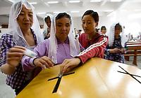 Une aveugle et d'autres fidèles chinois d'origine coréenne participent à la quête lors de la messe du dimanche matin à l'église catholique de Yanji, à Yanji, province de Jilin, en Chine, le 6 septembre 2009. Photo par Lucas Schifres/Pictobank