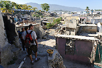 Andy Chaggar and EDV staff walking to the site of a damaged orphanage as part of a site assessment, Port-au-Prince, Haiti. EDV is committed to affecting permanent change in disaster-affected communities worldwide. Their role is to facilitate personal connections between volunteers and the survivors of disasters.  The charity is based on a proven model developed by several landmark organisations that have paved the way for citizens to become disaster volunteers. These landmark organisations have shown that supposedly ordinary people working together with the guidance of knowledgeable leaders can make an extraordinary difference in the lives of those affected by disaster..EDV believe that to provide meaningful relief and reconstruction assistance to disaster affected communities they have to do more than reconstruct buildings. They need to understand and address the factors that made a community vulnerable to the disaster in the first place. The charity's work is organised with these factors in mind so that they can affect change that far outlives their presence..EDV believes that survivor motivation is essential to the recovery of any disaster-affected community. Their operations will always be predicated on the idea that survivors may be traumatised, but they are not helpless. With this in mind, EDV encourages host communities to direct their own recovery. EDV believe that this empowerment is essential in helping survivors feel a renewed sense of control over their lives which will, in turn, help overcome the feelings of hopelessness that can follow a disaster and inhibit long term recovery. EDV also believe that social cohesion is of primary importance in any disaster-affected area. No amount of bricks or mortar will bring about sustainable improvement if communities fail to come together or are disrupted by relief efforts. Therefore, their operations will always aim to foster communication and cooperation within and between the communities they serve.