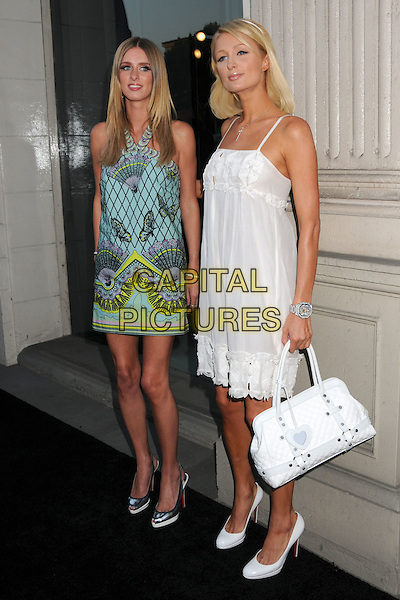 "NICKY HILTON & PARIS HILTON .""The Good Life"" Photographs by Murray Garrett and Slim Aarons Exhibition at Photographers Gallery, Los Angeles, California , USA,27 June 2008..Full length sisters print green blue butterfly dress white bag shoes Christian Louboutin wrist watch .CAP/ADM/BP.©Byron Purvis/Admedia/Capital Pictures"