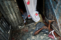 Haitian kids killing time in a shack in the slum of Cité Soleil, Port-au-Prince, Haiti, 24 July 2008. Cité Soleil is considered one of the worst slums in the Americas, most of its 300.000 residents live in extreme poverty. Children and single mothers predominate in the population. Social and living conditions in the slum are a human tragedy. There is no running water, no sewers and no electricity. Public services virtually do not exist - there are no stores, no hospitals or schools, no urban infrastructure. In spite of this fact, a rent must be payed even in all shacks made from rusty metal sheets. Infectious diseases are widely spread as garbage disposal does not exist in Cité Soleil. Violence is common, armed gangs operate throughout the slum.
