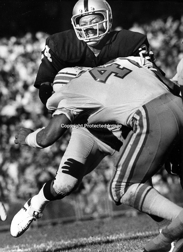 Oakland Raider defensive back Willie Brown puts a crushing hjit on running back. (1975 photo/Ron Riesterer)