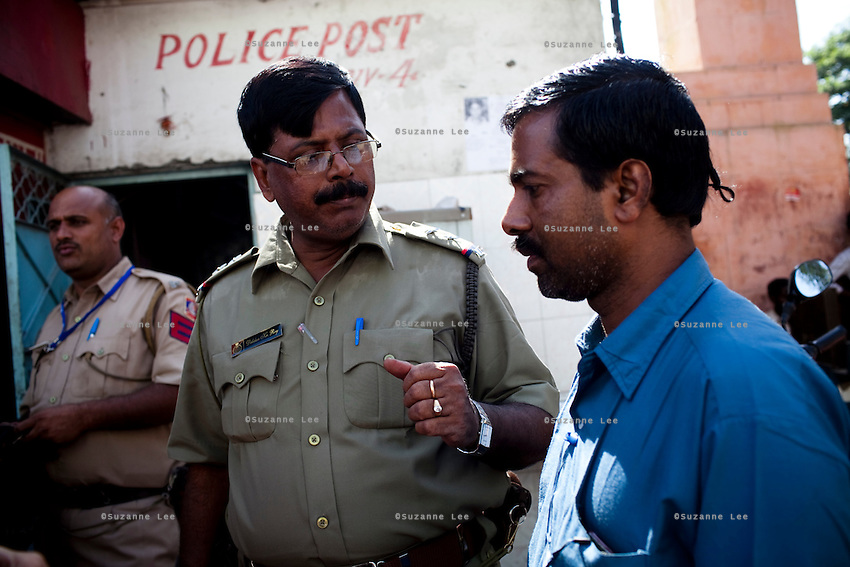Mr. Pathak speaks to a policeman about his daughter on 28th September 2010, on GB Road, Delhi's red light district, India..Mr. Kailash Pathak, a Hindu priest, has travelled to Delhi from his village in New Jalpaiguri, West Bengal, to look for his missing daughter, Khushbu Pathak aged 13, who was last seen in the custody of his neighbours in February this year and believed to have been sold to brothels in the capital, Delhi. The accused neighbours have since been arrested in Delhi but the girl is yet to be found. Photo by Suzanne Lee