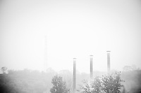 Daytime landscape view of smokestacks at a power plant facility near the Sānménxiá Dam on the Huang He in the Sānménxiá Shì Húbīn District in Hénán Province.  © LAN