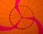 The seams and fabric make a symetrical pattern in brightly colored fabric at the very top of a hot-air balloon, visible from inside as the bag inflates.  © RickCollier.com.
