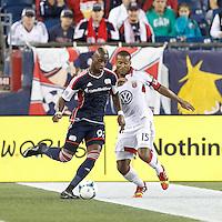New England Revolution forward Dimitry Imbongo (92) passes the ball as D.C. United defender Ethan White (15) defends. In a Major League Soccer (MLS) match, the New England Revolution (blue) defeated D.C. United (white), 2-1, at Gillette Stadium on September 21, 2013.
