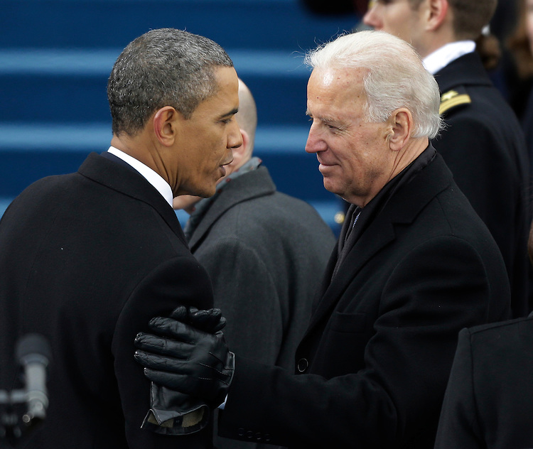 President Barack Obama, left, speaks to Vice President Joe Biden following the ceremonial swearing-in at the U.S. Capitol during the 57th Presidential Inauguration in Washington, Monday, Jan. 21, 2013. (AP Photo/Pablo Martinez Monsivais)