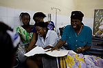 """Women from """"Jesus is Lord ministries"""" pray for Mommy, screaming and chanting, pouring oil on her. They were according to the staff called by a family member of Mommy. Nurse Bintu Janneh (green dress) and sister Kristiana Seymon watch. Mommy is still alive. Mommy delivered and died from postpartum bleeding at the PCMH (Princess Christian Memorial Hospital), Freetown, Sierra Leone.."""