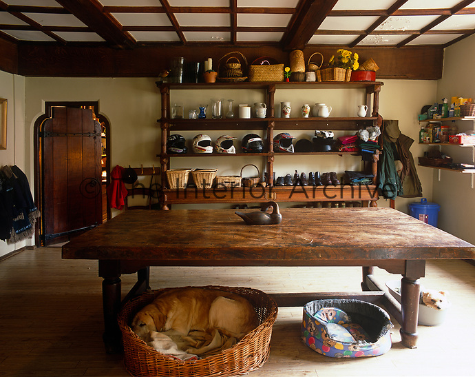 The utility room is dominated by a sturdy wooden table while open shelving is stacked with shoes and helmets