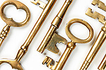 Bunch of old brass keys on white close-up Conceptual abstract background texture