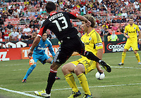 WASHINGTON, DC - AUGUST 4, 2012:  Chris Pontius (13) of DC United sends a cross past Chad Marshall (14) of the Columbus Crew during an MLS match at RFK Stadium in Washington DC on August 4. United won 1-0.