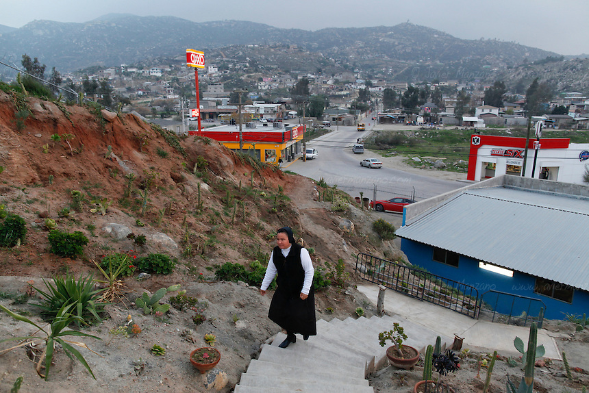 "Mother Ines, the Catholic nun who manages the ""Casa Migrante"", an immigrant shelter in Tecate, Baja California, Mexico, walks up the steps of her garden at the facilities on February 7, 2013.  This immigrant shelter houses and feeds thousands of immigrants every year. With a total capacity of 40 beds, male migrants can stay in the premises for a total of 4 nights before moving on. Places such as Casa Migrante are popular amongst immigrants and deportees making their way back into the United States. (Javier Manzano / For The Washington Post)."