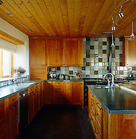 The kitchen of this contemporary house in New Mexico glows with the warmth of pine used both in the construction of the ceiling and the kitchen cupboards