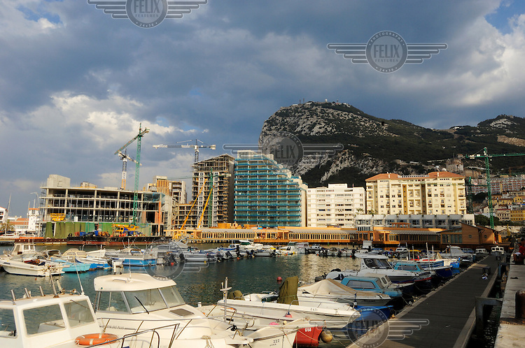 A view from reclaimed land of pleasure boat harbour, and new luxury apartment buildings, with the Rock 0f Gibralter rising behind.