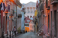 Steep narrow street with colourful painted houses in the old town, with a view to the Assemblea da Republica or Assembly of the Republic, the Portuguese parliament building, Lisbon, Portugal. The parliament has been housed in the Palacio de Sao Bento or St Benedict Palace, an old Benedictine monastery, since 1834. Picture by Manuel Cohen